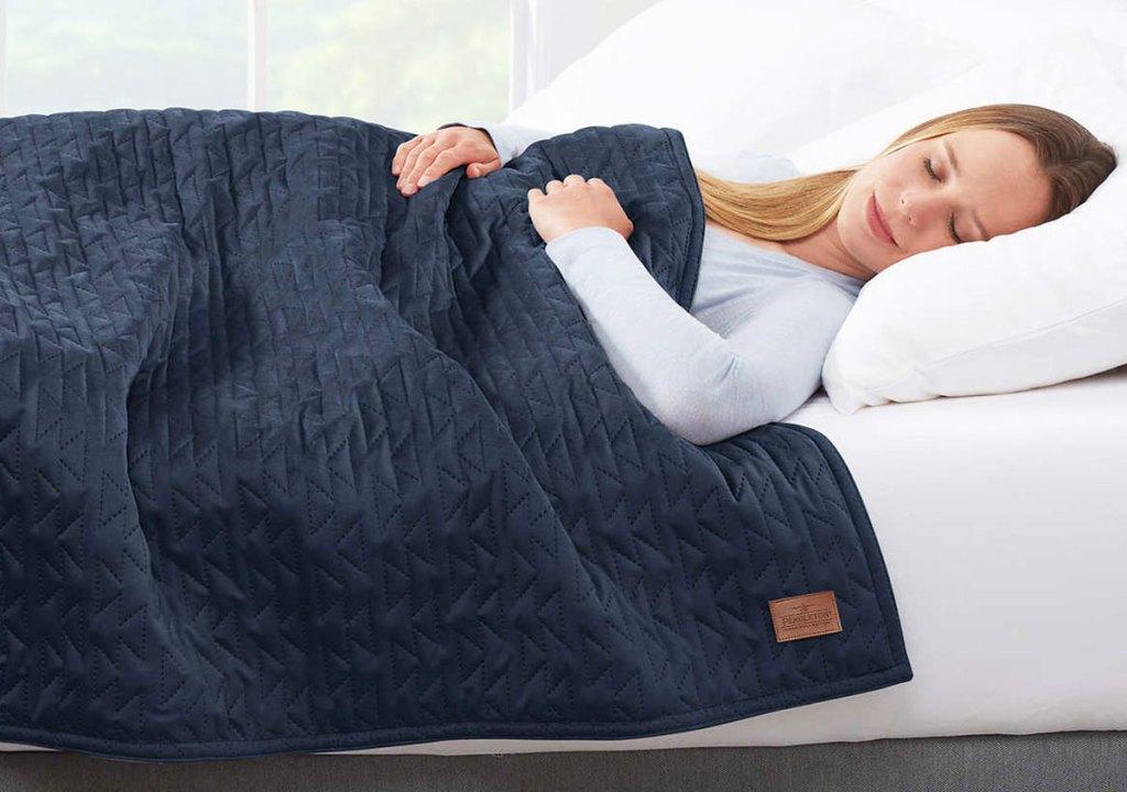 wanita tidur di tempat tidur dengan selimut berbobot biru tua di atasnya