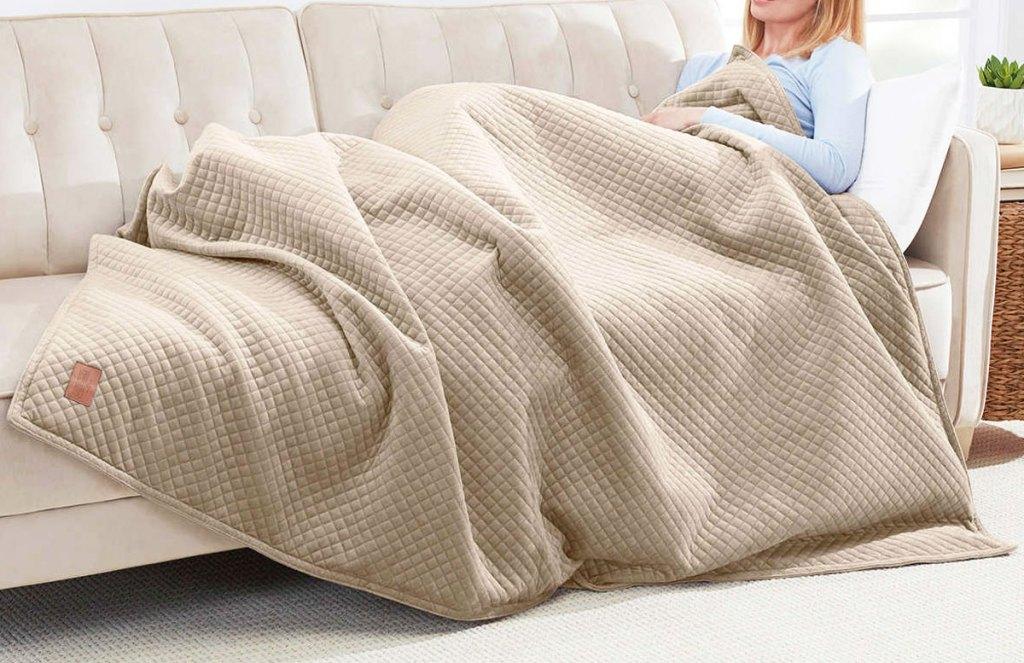 wanita yang duduk di sofa dengan selimut berbobot cokelat di atasnya