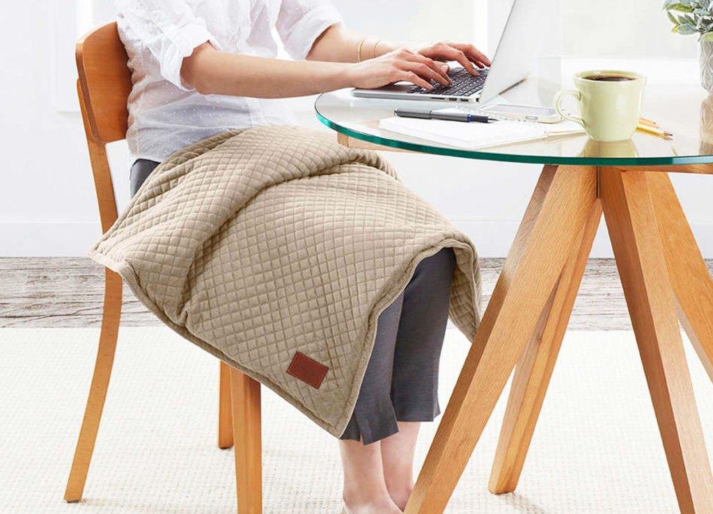 seorang wanita yang duduk di meja bekerja dari laptop dengan selimut berbobot cokelat di pangkuannya
