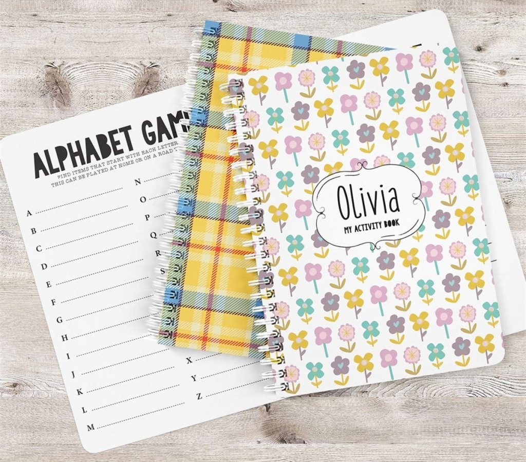 two spiral bound printed notebooks with personalized names on them with an alphabet games activity sheet beneath them