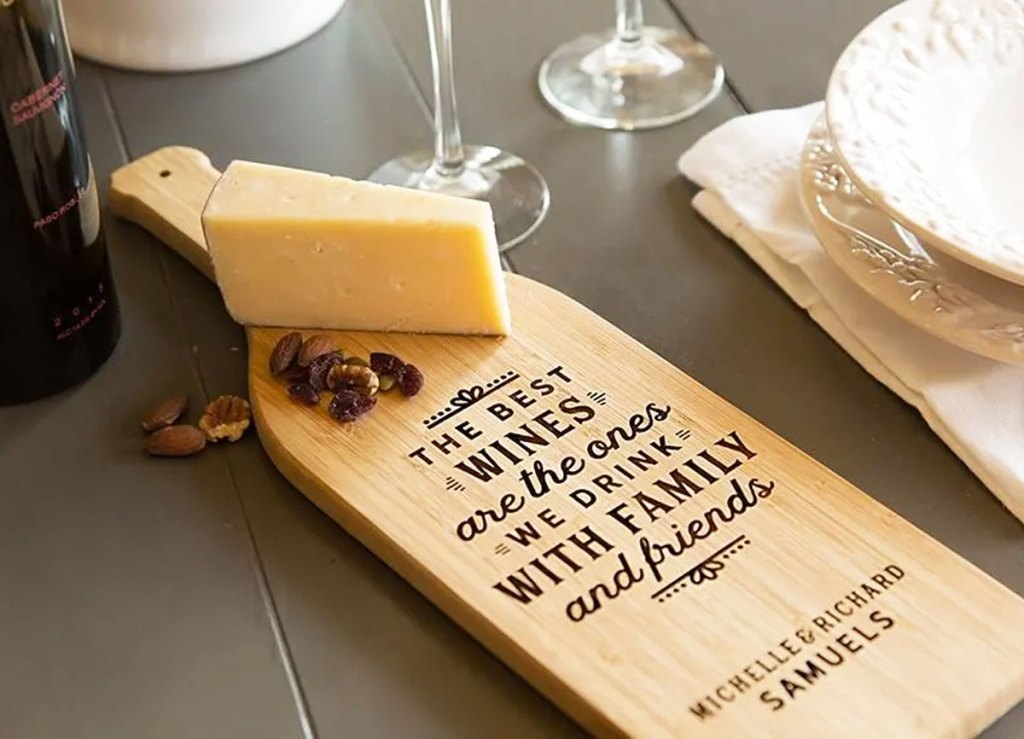 wine bottle shaped cutting board with personalized engraving on it near block of cheese and wine glasses