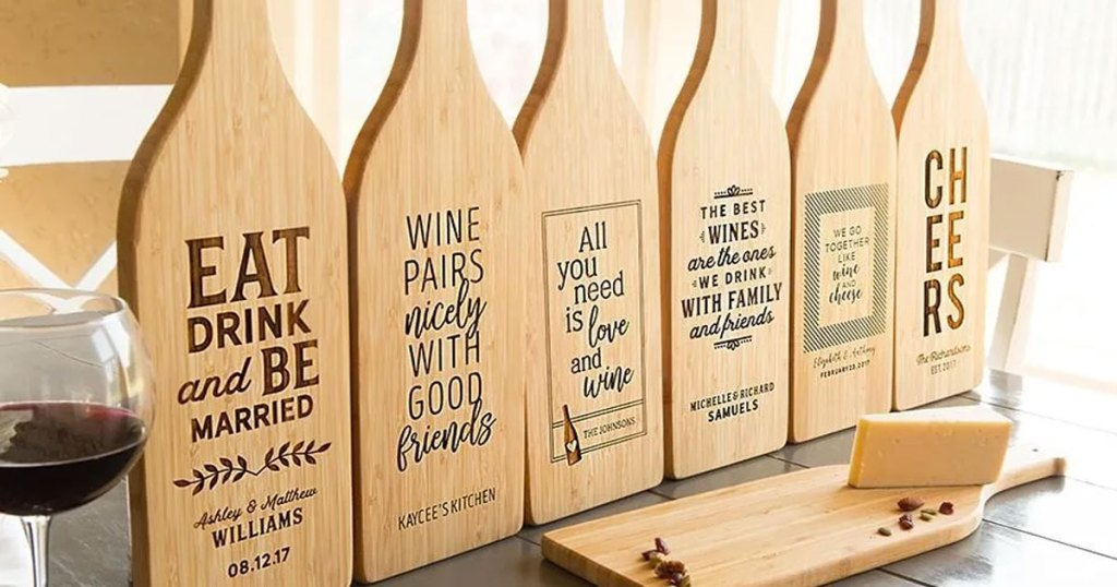 multiple wine bottle shaped wood cutting boards with wine-themed signs on them all lines up near a glass of wine