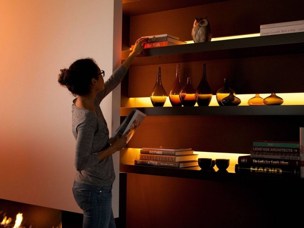 woman stacking books on shelf that are lit up