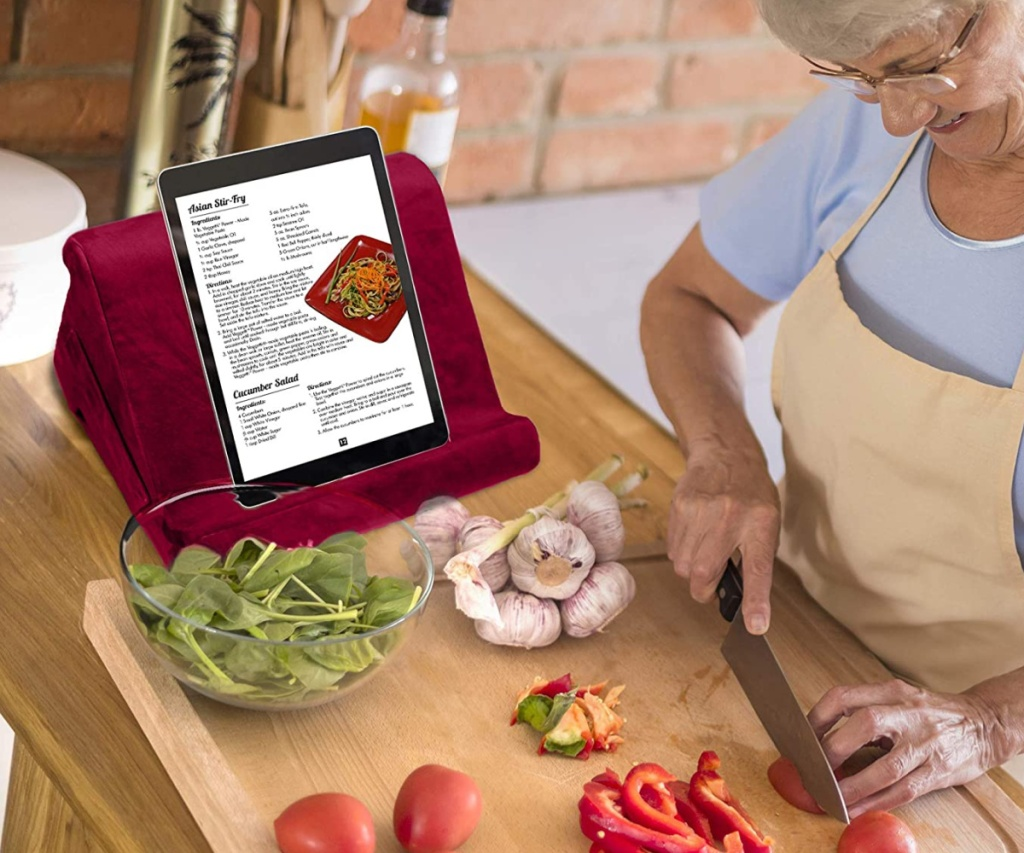 woman cutting vegetable in kitchen and tablet with recipe open on maroon pillow pad