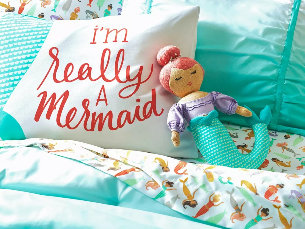 mermaid throw pillows on a child's bed