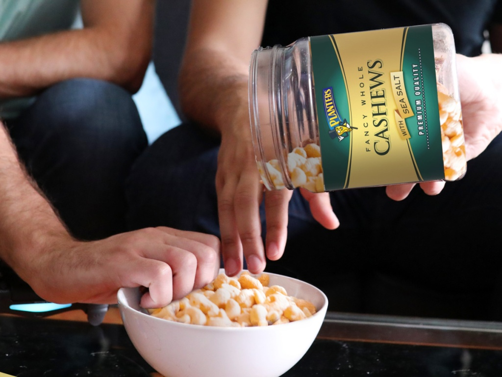 hand pouring cashews from a large jar into a white bowl