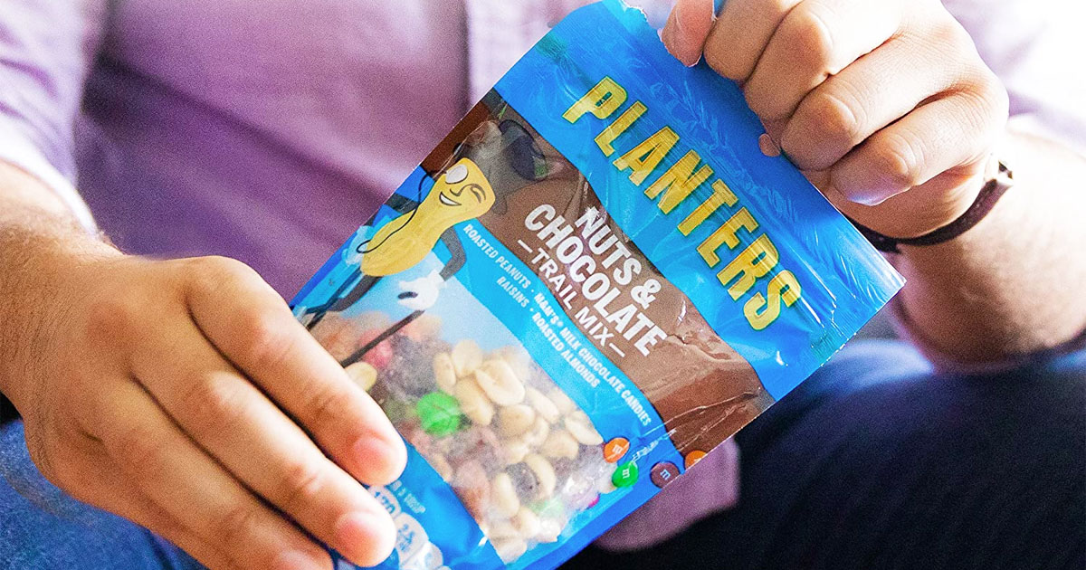 man holding a blue bag of planters trail mix in both hands