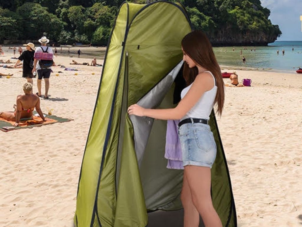 woman walking into popup privacy tent on beach