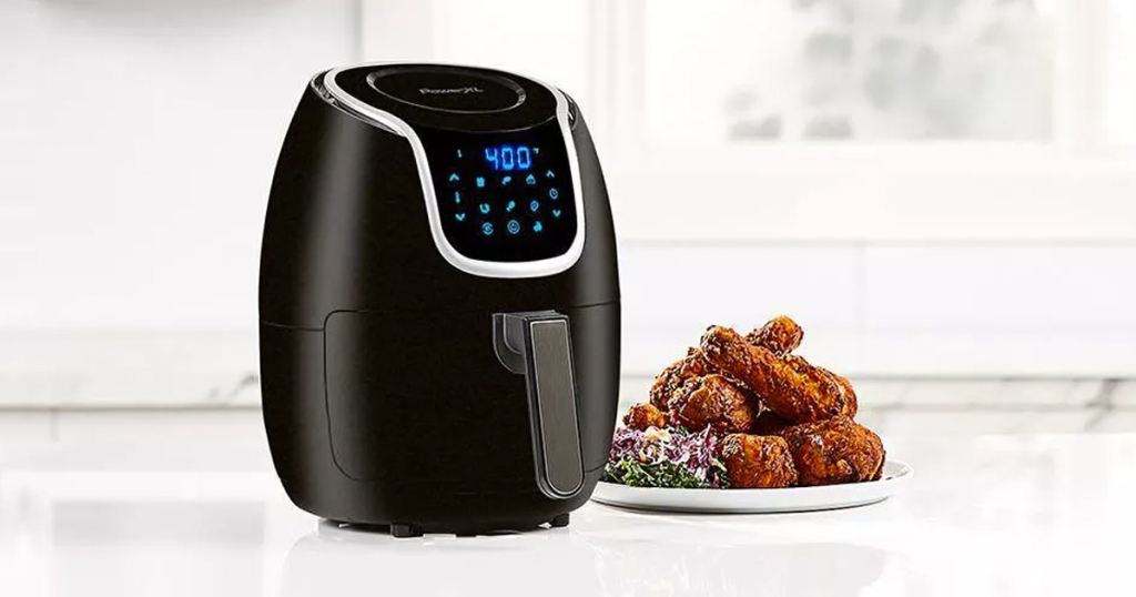 black air fryer on kitchen counter next to plate of fried chicken