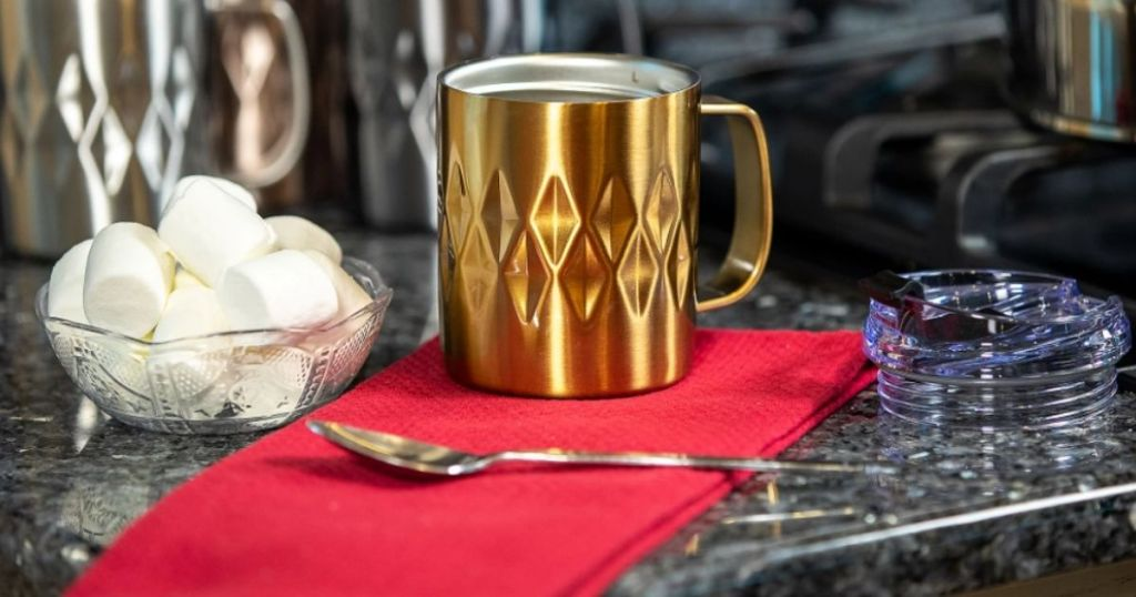 mug with a spoon and marshmallows near it