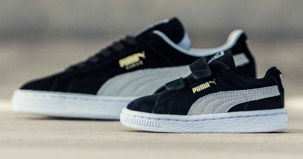 pair of matching adult and kids puma sneakers in black with white stripe down the sides