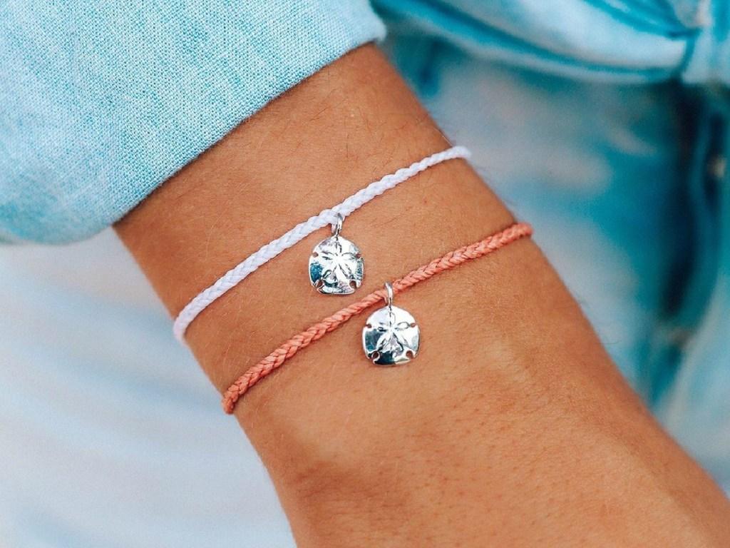woman wearing two sand dollar pura vida bracelets
