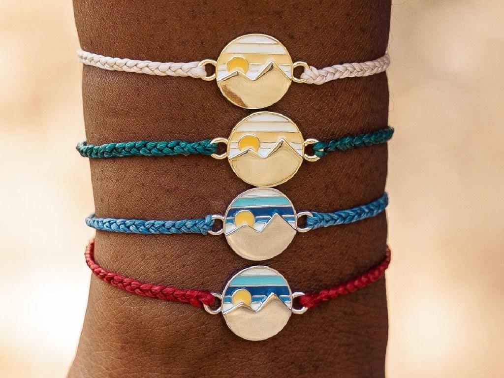woman wearing multiple twin peaks charm bracelets