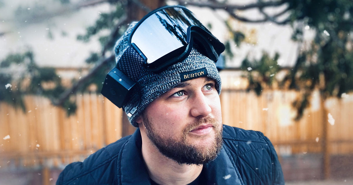 man standing outside in a black jacket with a grey beanie and black pair of ski goggles on top of his head