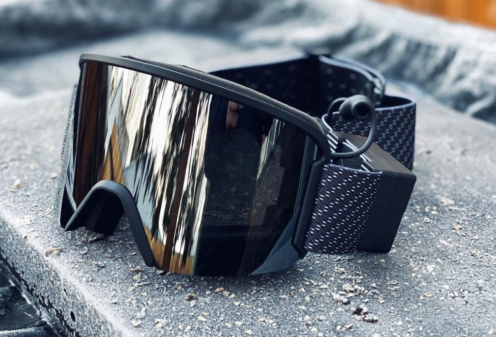 pair of black ski goggles on a grey bench outside