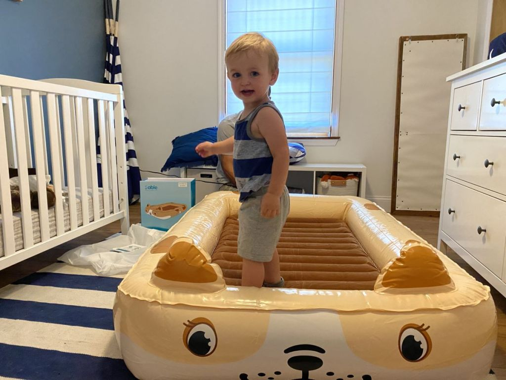 boy standing on an inflatable bed