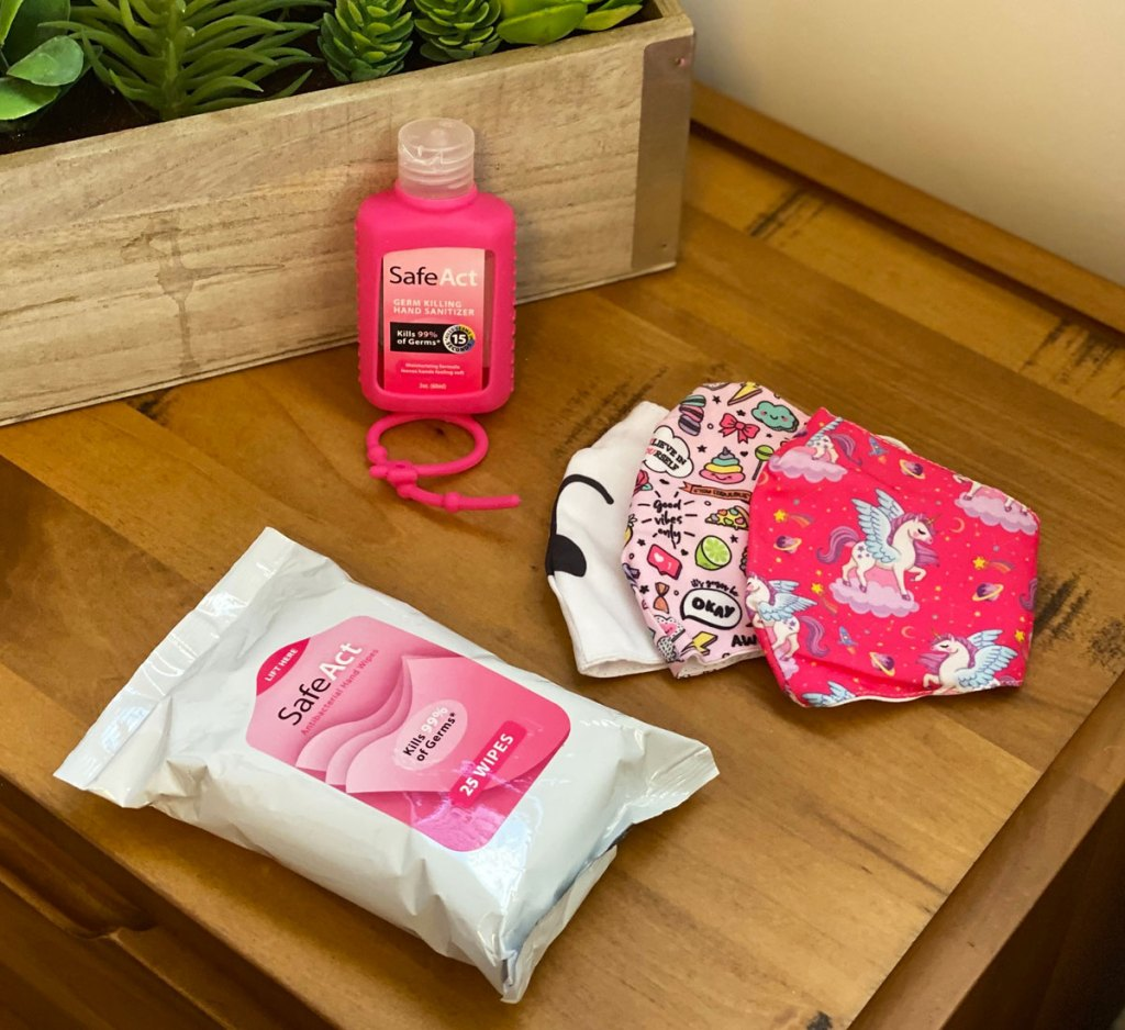 pack of SafeAct wipes, pink hand sanitizer, and set of 3 reusable face masks on a wood table