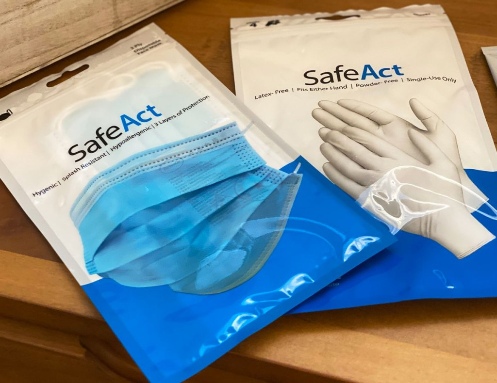 pack of SafeAct disposable face masks and gloves on a wood table