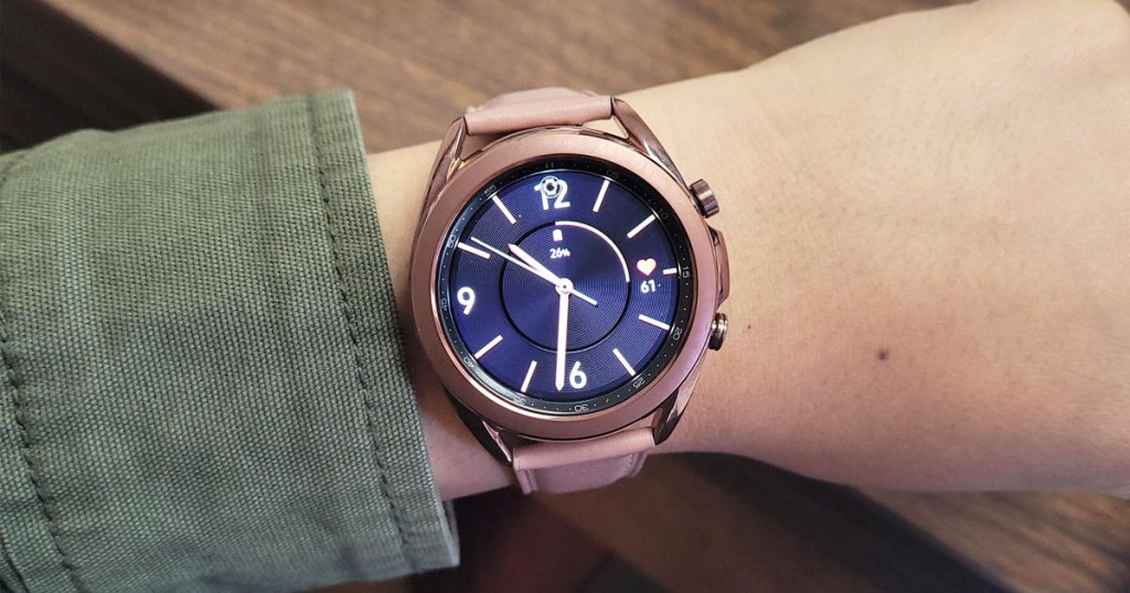 woman in olive green jacket with a pink Samsung galaxy watch 3 on her wrist