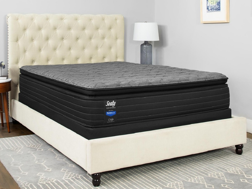black sealy mattress on a white bed in a bedroom