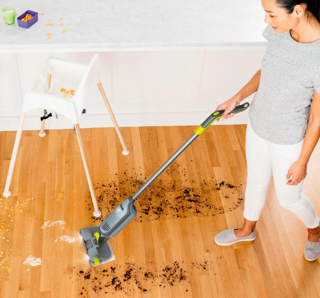 woman in grey shirt and white pants using a grey shark vacmop to clean up dirt and crumbs off hardwood floor