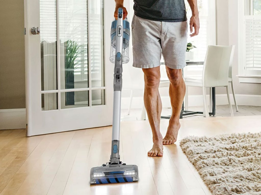 man pushing a shark cordless vacuum along hardwood floor in home