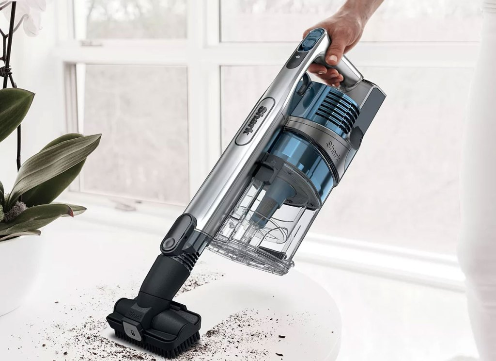 person using a shark cordless vacuum with brush attachment to clean up soil from plant