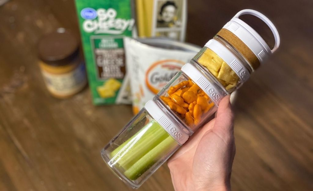 A hand holding snacks in jars