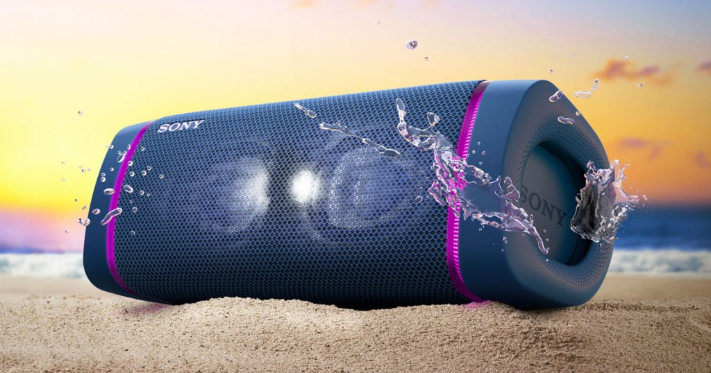 navy blue sony portable speaker with purple led lights on either side in sand with water splashes around it