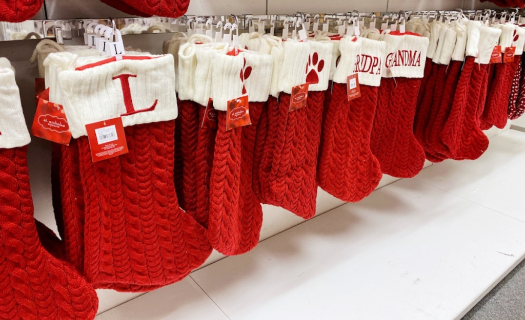 in store shelf with multiple monogram st nicholas square knit stockings in red
