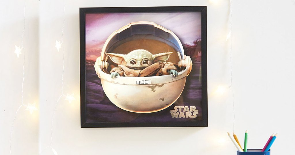 star wars baby yoda wall art on white wall with string lights around it