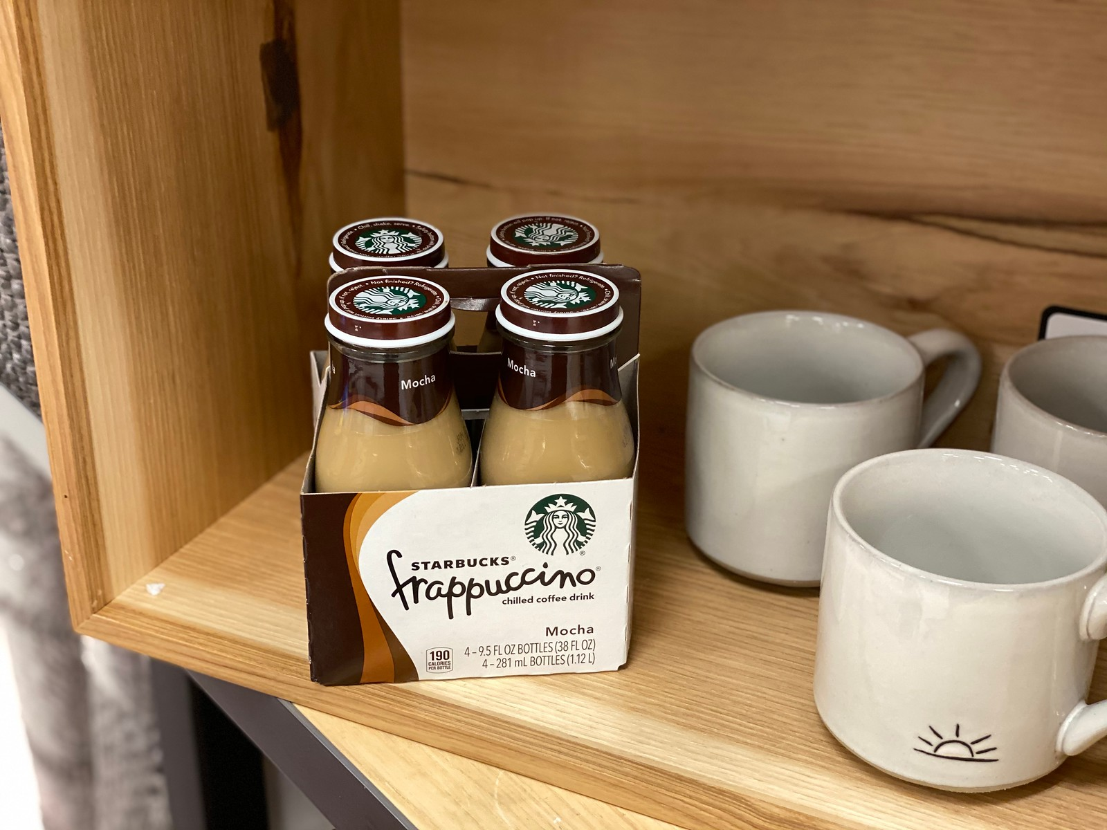 Starbucks Frappuccino on store shelf next to coffee cup
