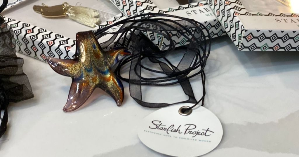 Starfish Project Necklace against jewelry boxes