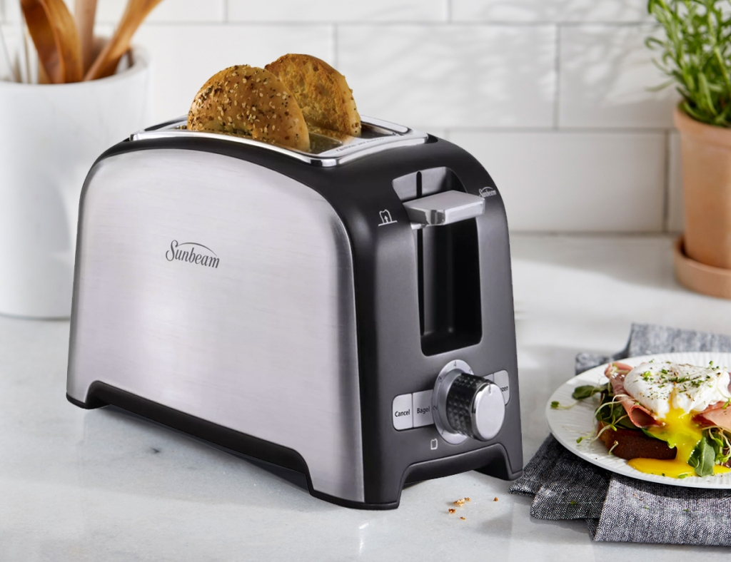 stainless steel toaster on kitchen counter with bagel slices inside