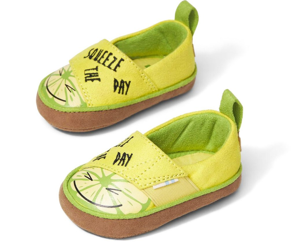 pair of yellow and green baby sneakers with lemons that say squeeze the day
