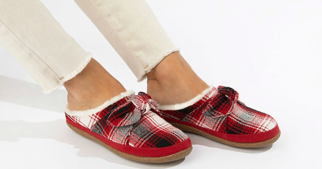 woman in cream colored skinny jeans with pair of red plaid slippers on her feet with matching bows on top