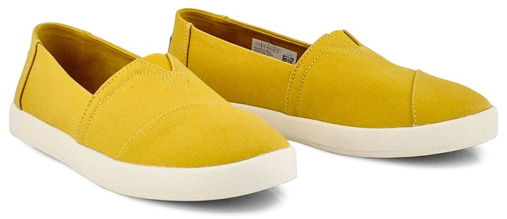 pair of yellow women's slip on toms shoes