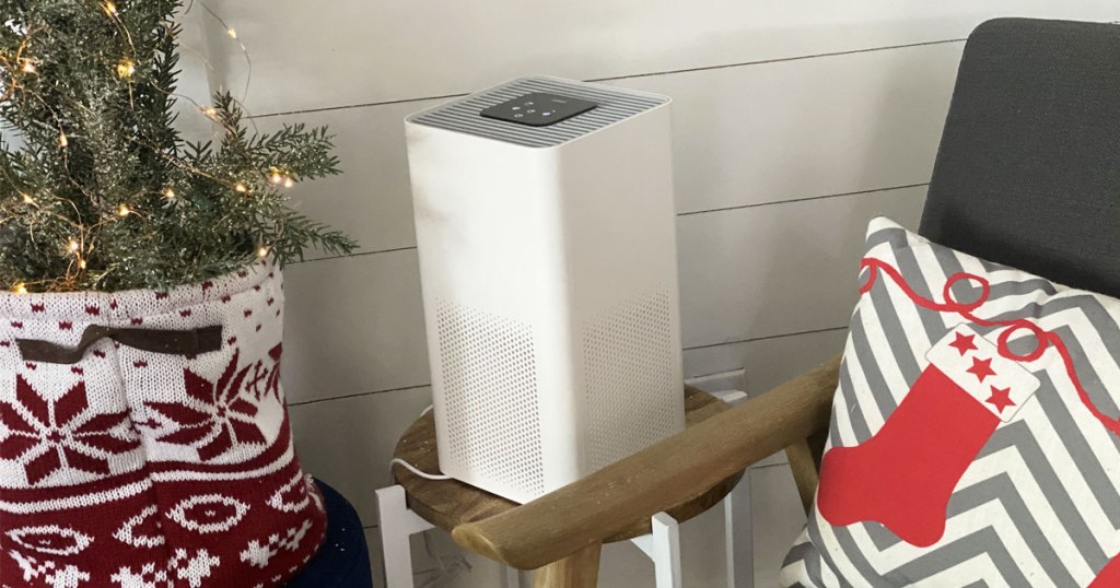 white air purifier sitting on a side table near a chair with christmas throw pillow and small christmas tree
