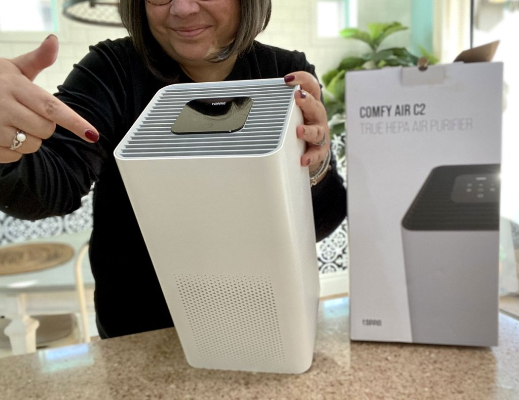 woman holding and pointing at a white square shaped air purifier