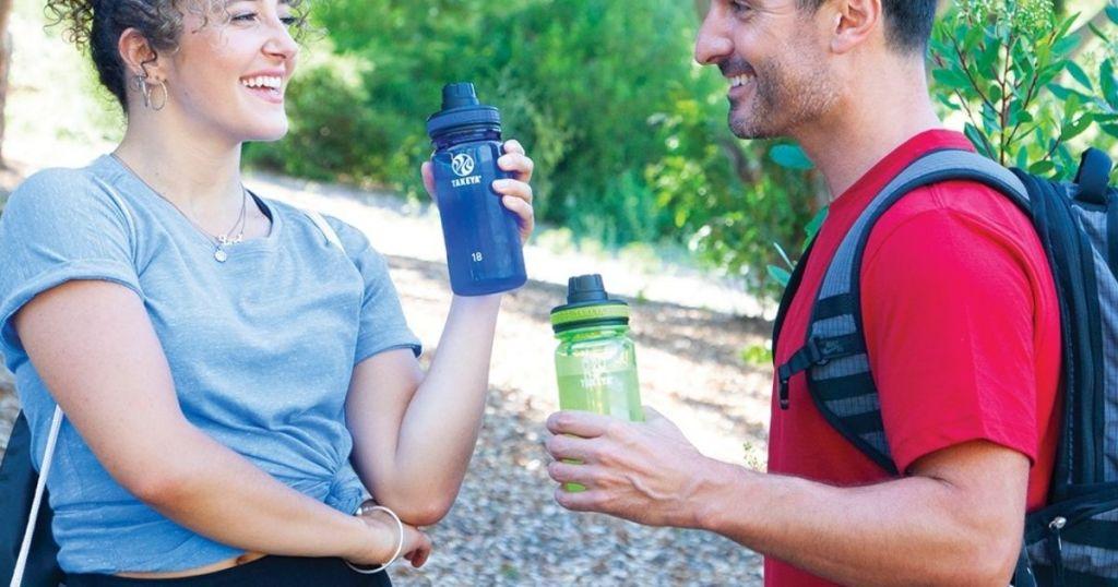 man and lady holding Takeya Tritan Water Bottles