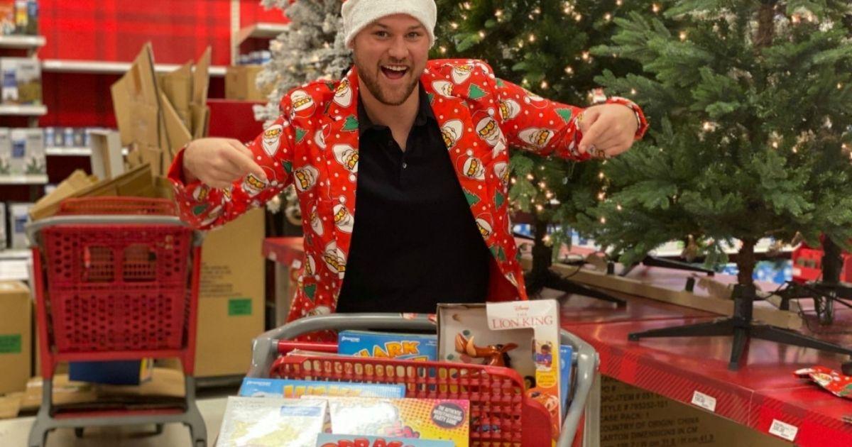 Man in santa hat pointing at Target cart full of Games