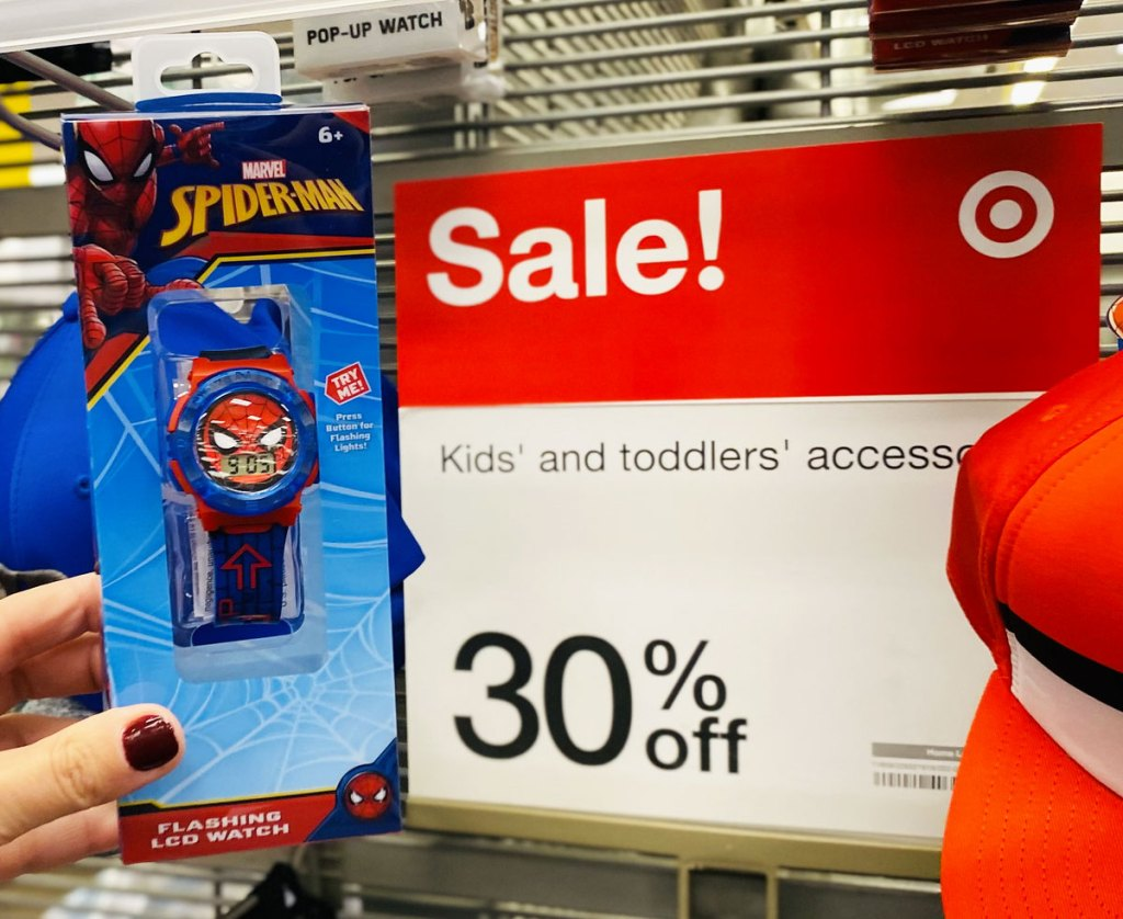 woman holding up a kids spiderman watch next to a 30% off sale sign at target