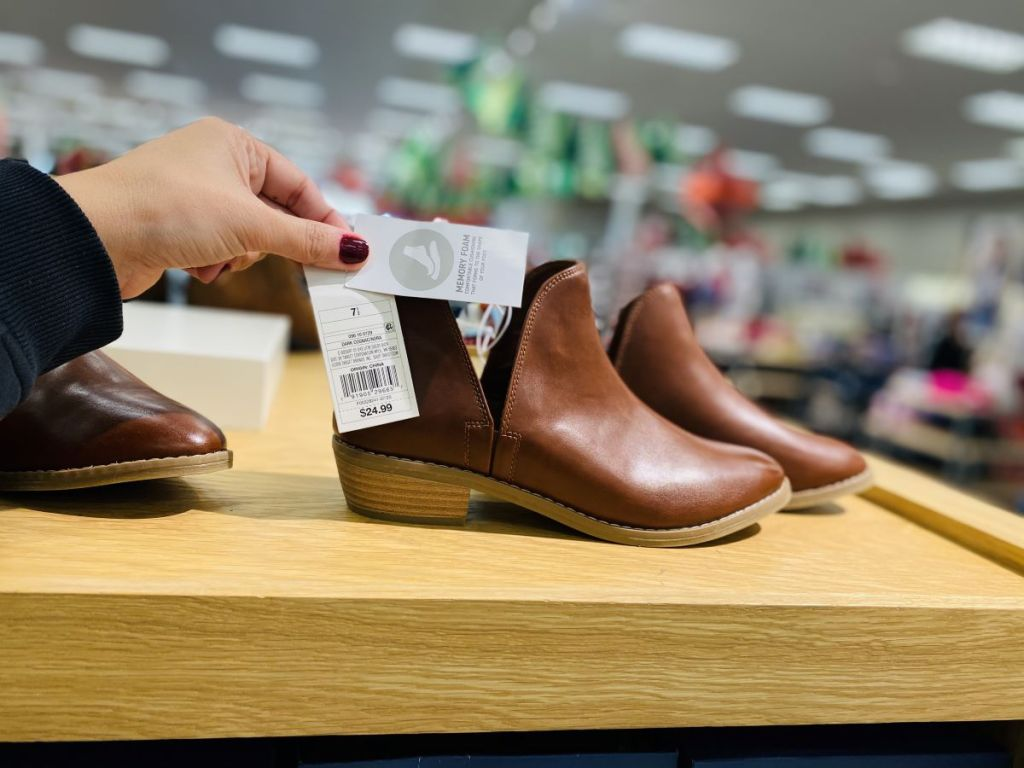 hand holding a tag on a pair of women's boots