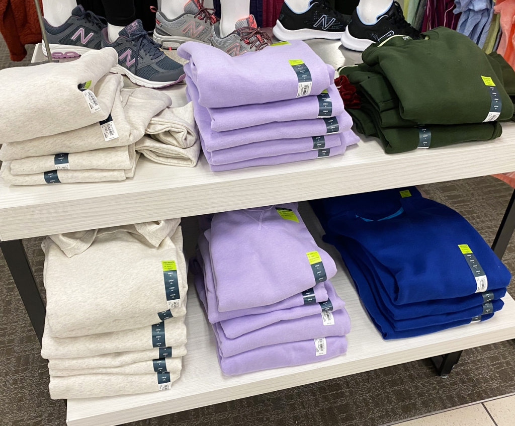 white display shelves with stacks of folded women's sweatshirts in various colors