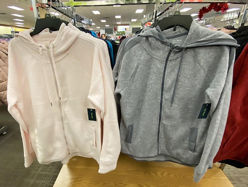 light pink and grey zip-up women's hoodies on hangers on display rack at kohl's