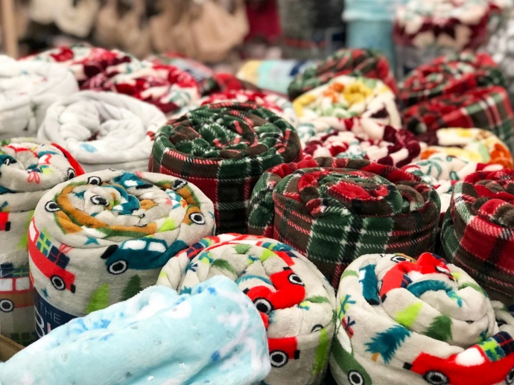 display of rolled up plush blankets in various prints at kohl's