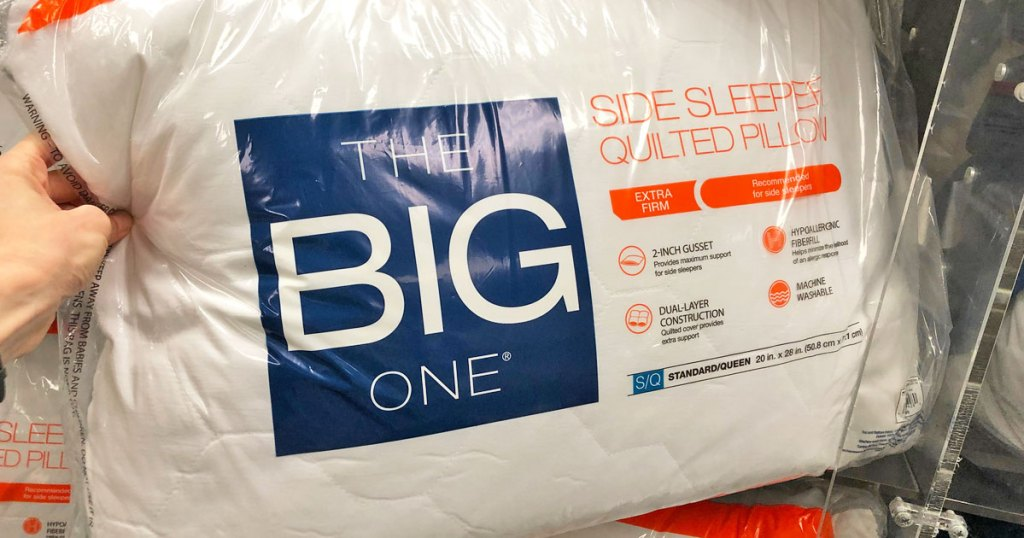 woman holding up the big one quilted side sleeper pillow in plastic packaging