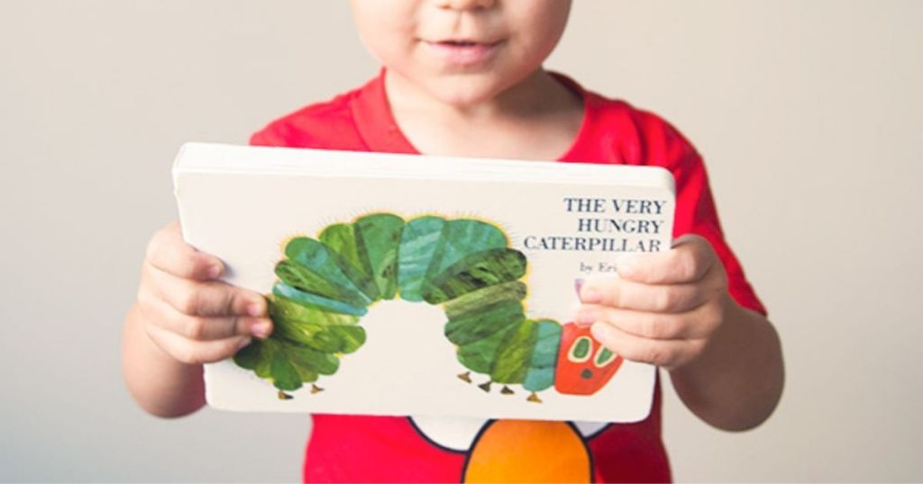 Child holding The Very Hungry Caterpillar Board Book