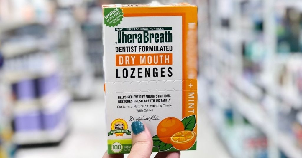 hand holding a box of lozenges