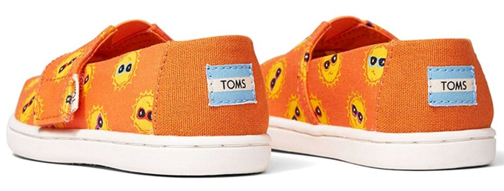 pair of orange tiny toms shoes with sunshines wearing sunglasses